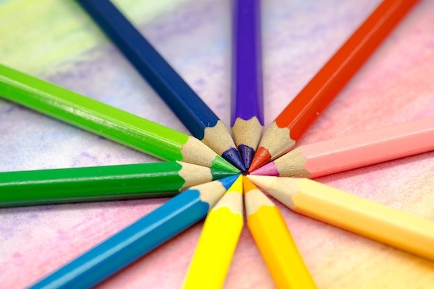 Large colored pencils stacked in a circle close-up on a colored background with colored pencils Free Photo