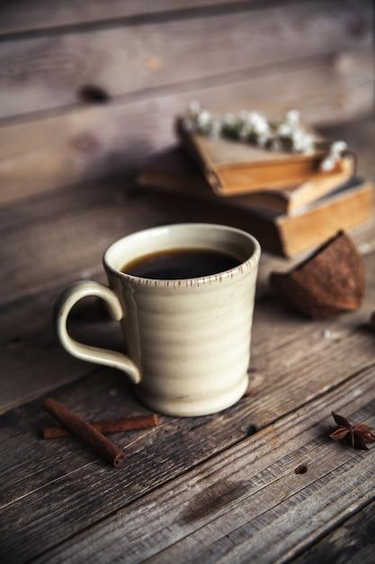 ヴィンテージの木製の背景にコーヒーの大きなカップ。春の花と本。 Premium写真