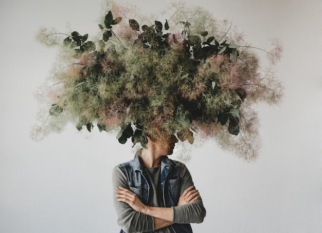 Large decorative bouquet made of green leaves and moss hangs over man's head Free Photo