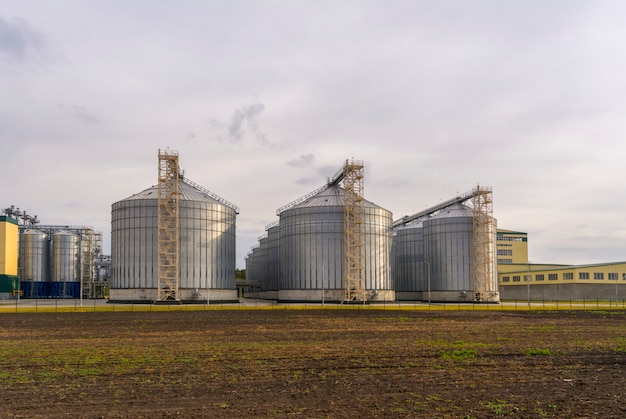 A large factory for the processing of grain. large elevator in the field. Premium Photo