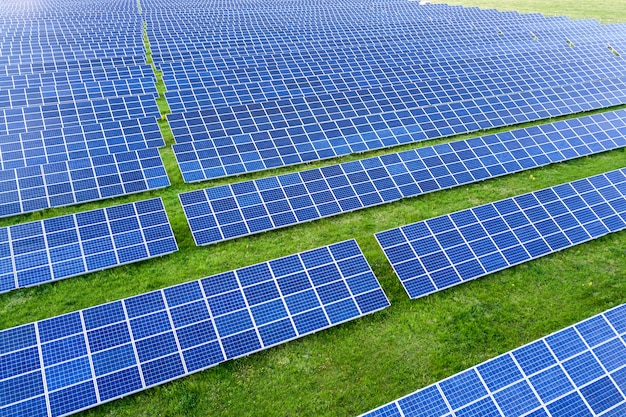Large field of solar photo voltaic panels system producing renewable clean energy on green grass background. Premium Photo