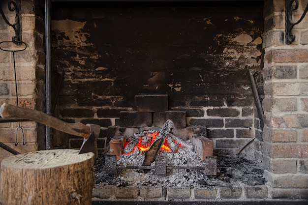 Large fireplace with a burning fire and decorative items Free Photo