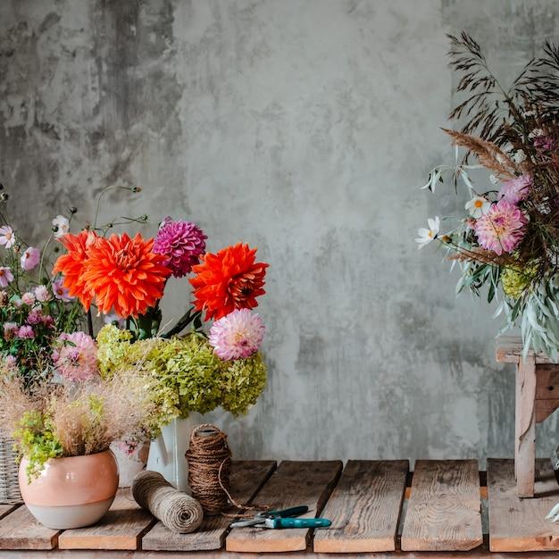 Large floral arrangement bouquet on the desktop florist on the background of a concrete wall Premium Photo
