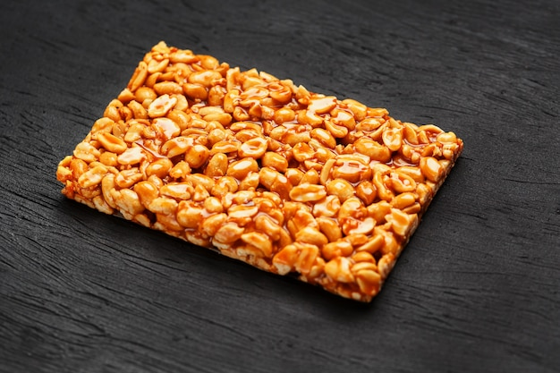 A large golden tile of peanuts, a bar in a sweet molasses. kozinaki useful and tasty sweets of the east Premium Photo