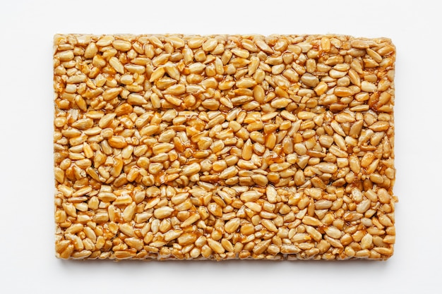 A large golden tile of sunflower seeds, a bar in a sweet molasses. kozinaki useful and tasty sweets of the east Premium Photo
