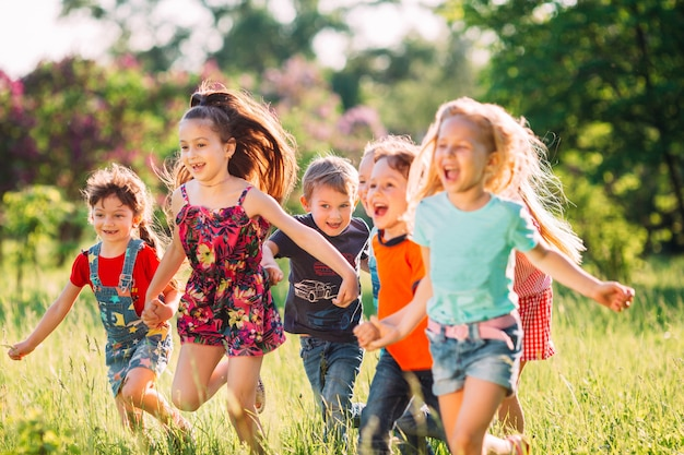 Large group of kids, friends boys and girls running in the park on sunny summer day in casual clothes . Premium Photo