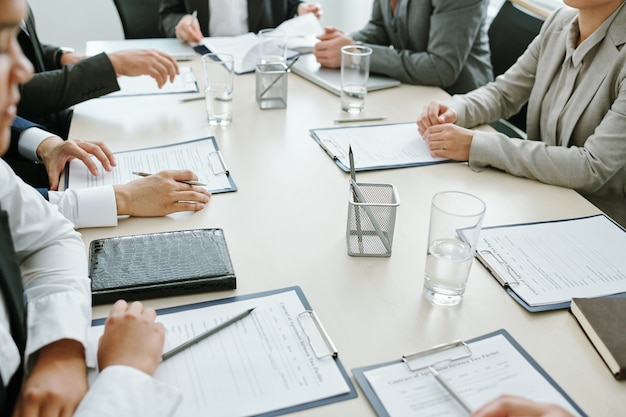 Большая группа деловых партнеров, коллег или участников конференции изучает финансовые документы или контракты на встрече в зале заседаний. Premium Фотографии