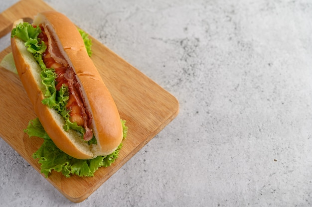 Large hot dog on wood cutting board Free Photo