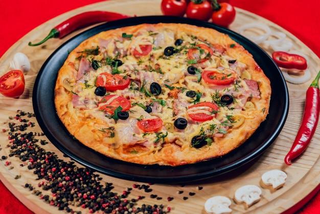黒いプレートに大きな温かいピザ。 Premium写真