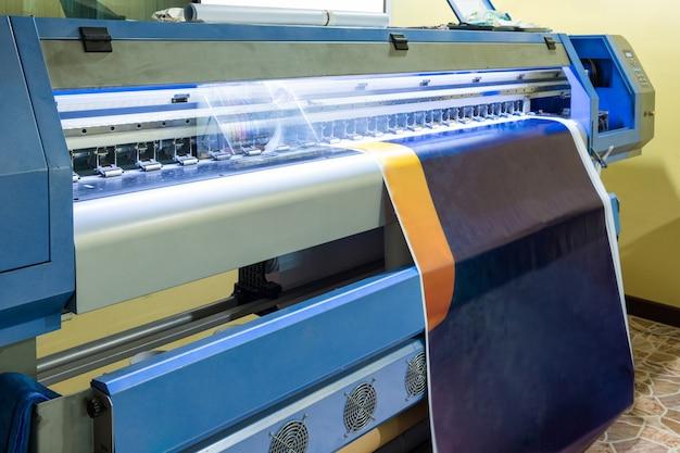 Large inkjet printer with head working on blue vinyl Premium Photo