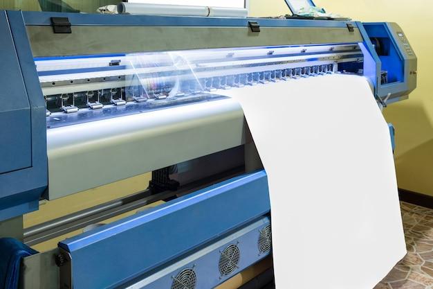 Large inkjet printer with head working on white blank vinyl Premium Photo