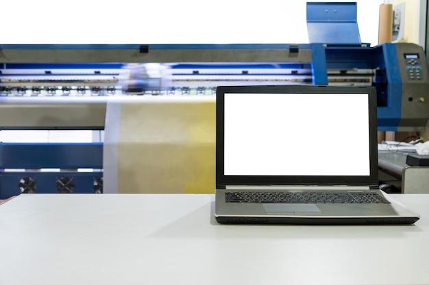 Large inkjet printer working on vinyl banner with laptop Premium Photo