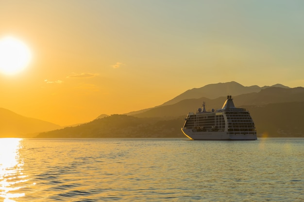 A large liner sails in the rays of the sunset along the boka kotorska bay. montenegro. Premium Photo
