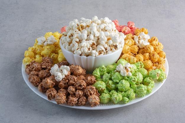 Un grande piatto di caramelle popcorn rivestite con una ciotola di popcorn nel mezzo su marmo. Foto Gratuite