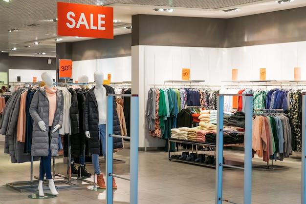 Большой красный знак с надписью sale в большом бутик-магазине одежды. большая распродажа одежды в большом современном торговом центре, тц Premium Фотографии