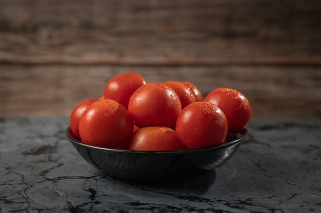 Large red tomatoes on a black plate, on a granite table Premium Photo