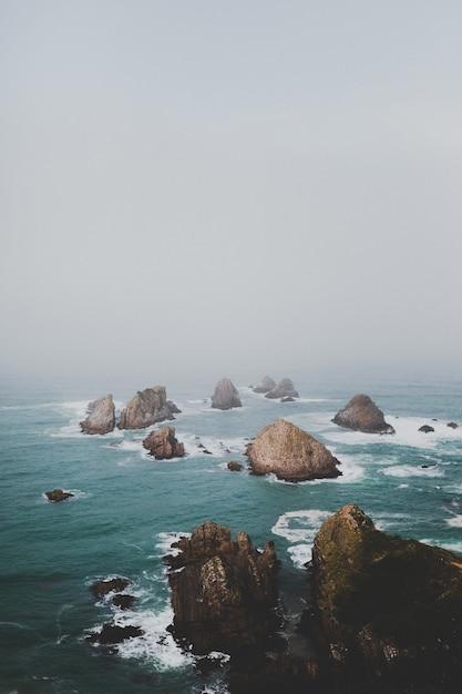 ナゲットポイントアフリリの大きな岩、霧の背景を持つニュージーランド 無料写真
