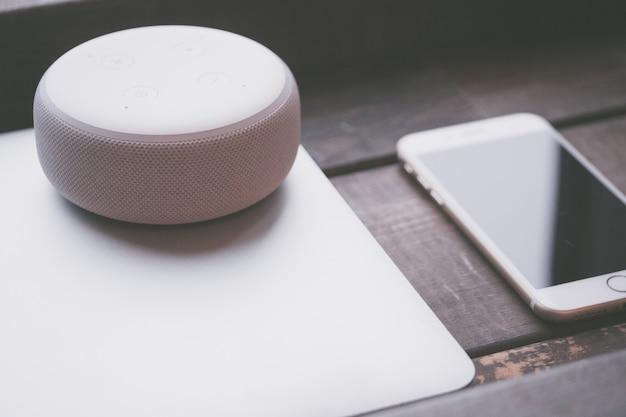 灰色のラップトップ上の大きな丸い白いbluetoothスピーカーと側面のスマートフォン 無料写真