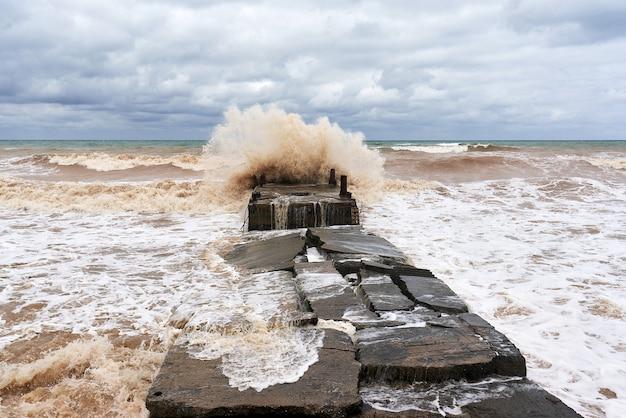 水しぶきのある大きな海の波が石の防波堤に衝突 Premium写真