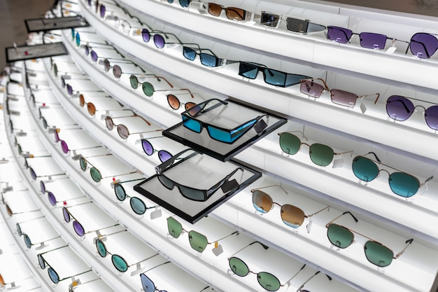 A large selection of optics located on a retractable white stand with various sunglasses of different shapes. Premium Photo