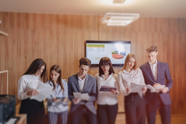 Large team of people is working at one table for laptops, tablets and papers, on the background a large tv set on a wooden wall Premium Photo