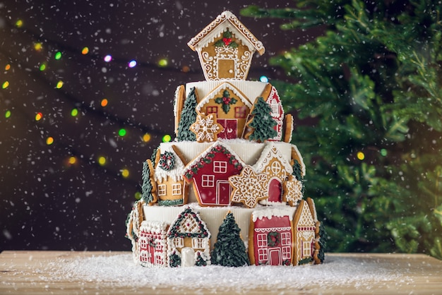 Large tiered christmas cake decorated with gingerbread cookies and a house on top. tree and garlands  background. Premium Photo
