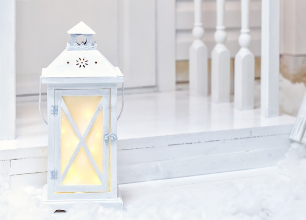 Large vintage white street lamp standing on the porch with snow Premium Photo