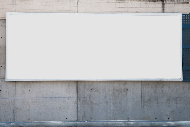 A large white blank billboard on concrete wall Premium Photo
