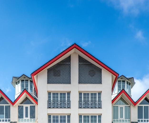 Большое белое здание с красной крышей под голубым небом Бесплатные Фотографии