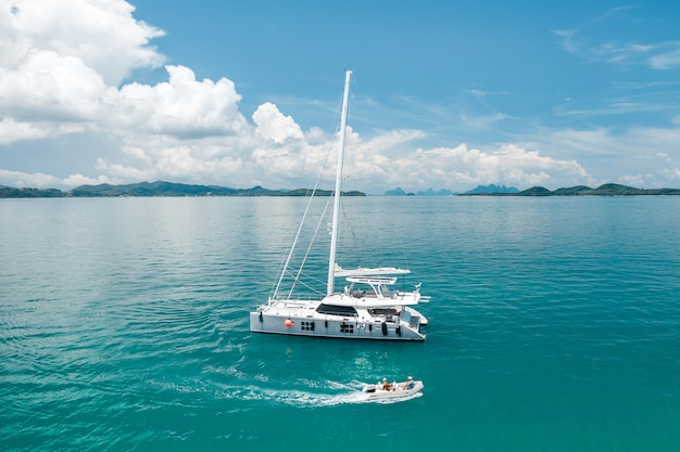 A large white yacht floating in the warm azure ocean, next to which a small boat floats, leaving waves behind it. sailing ships. rest time. enjoyment. expensive vacation. photo from a quadrocopter. Premium Photo
