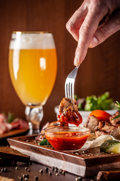 A large wooden board with a kebab of beef, pork and chicken. Premium Photo