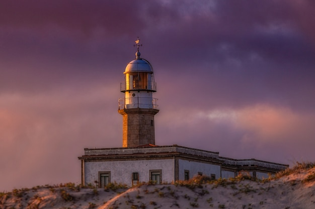 Larino lighthouse under a cloudy sky during the sunset in the evening in spain Free Photo