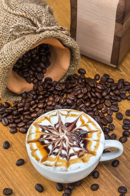 Larte art coffee cup on wood table with traditional coffee beans and grinder Premium Photo