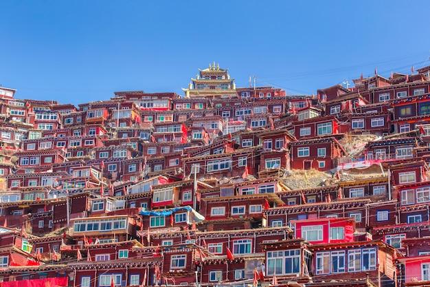 日の出日と背景のlarung gar(仏教学院)でトップビュー修道院は青い空、四川省、中国です。 Premium写真