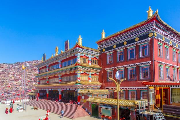 日の出日と背景のlarung gar(仏教学院)で赤い修道院は青い空、中国四川省です。 Premium写真