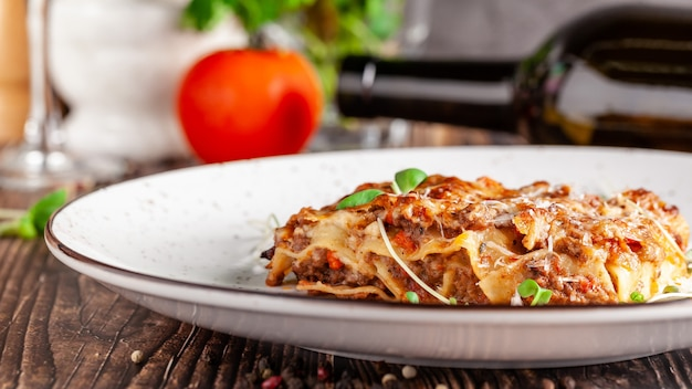 Lasagna with minced meat, bechamel sauce and parmesan cheese. Premium Photo