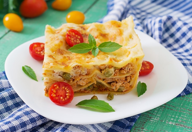 Lasagna with minced meat, green peas and sauce Premium Photo