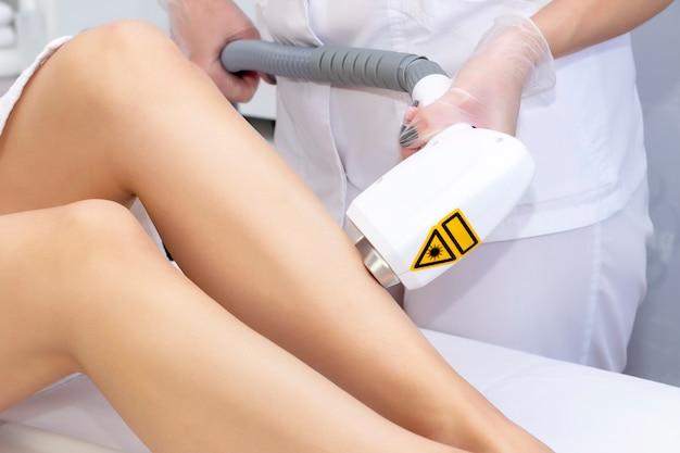 Лазерная эпиляция ног. лазерная эпиляция и косметология. процедура удаления волос косметологическая. лазерная эпиляция и косметология. косметология и концепция spa Premium Фотографии