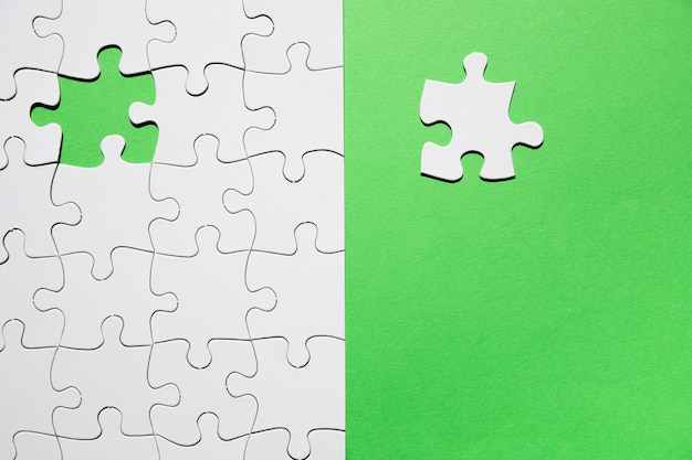 Last piece of puzzle missing on green background to complete the mission Free Photo