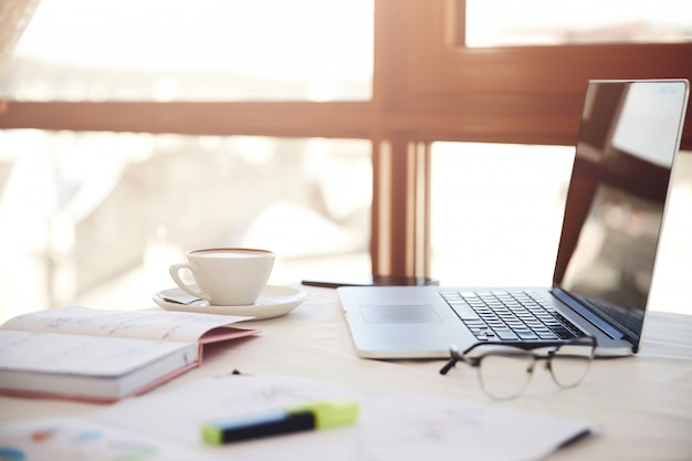 노트북, 커피 한잔, 안경 및 문구와 함께 책상의 측면 전경 무료 사진