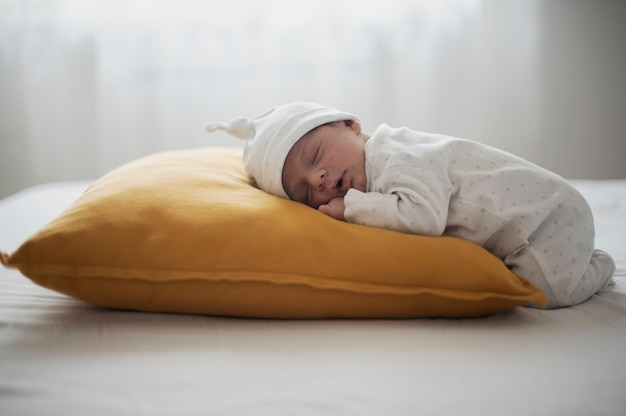 Lateral view baby sleeping on a yellow pillow Free Photo