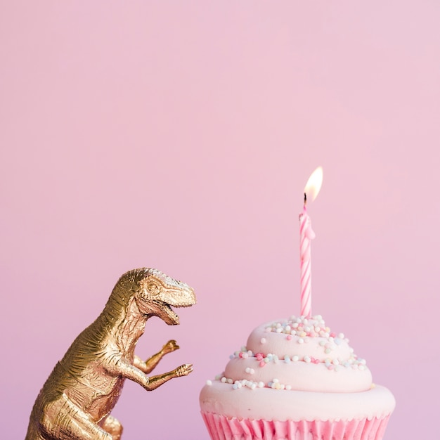 Lateral view birthday cake and plastic dinosaur Free Photo