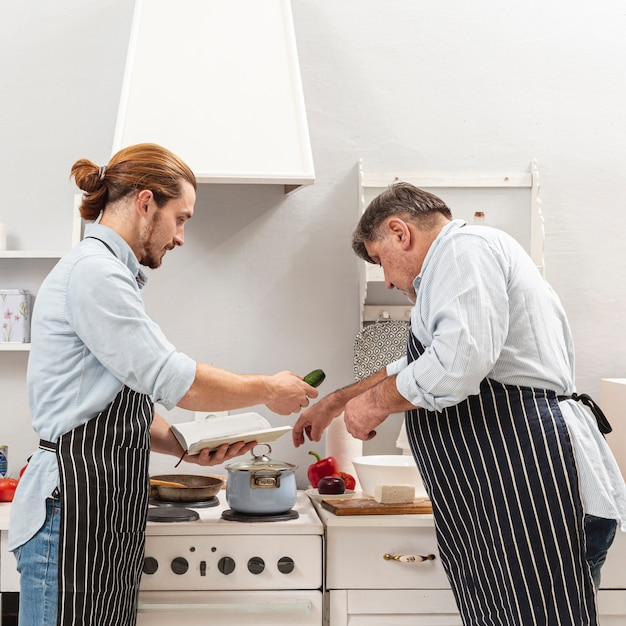 Lateral view father and son cooking together Free Photo