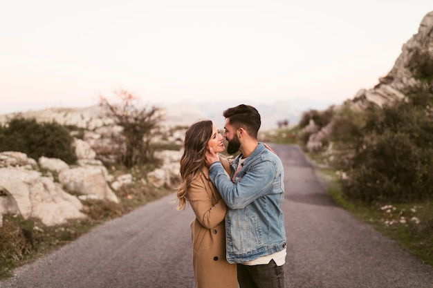 Lateral view lovely couple kissing on mountain road Free Photo