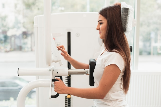 Lateral view patient using medical workout machine Free Photo