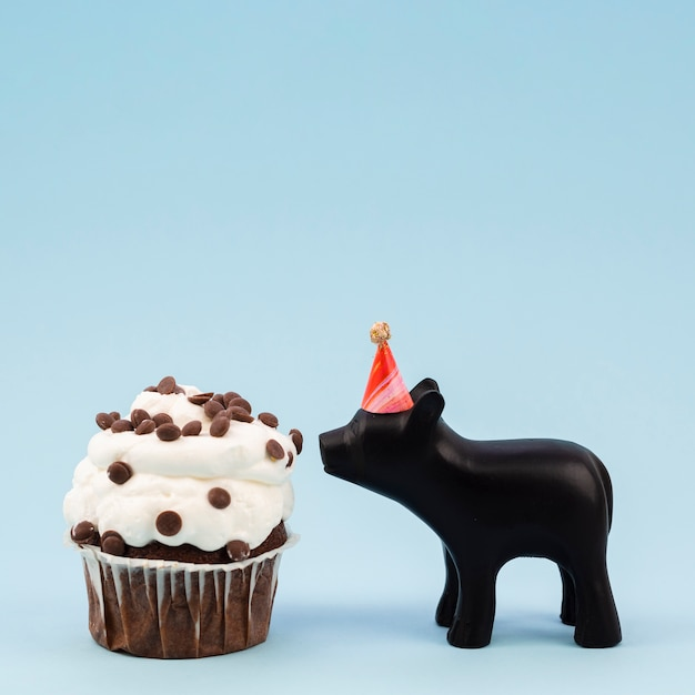 Lateral view tasty muffin and chocolate pig Free Photo