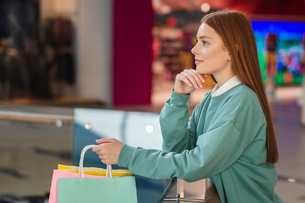 Lateral view thinking woman holding shopping bags Free Photo