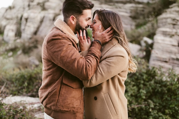 Lateral view young couple kissing in nature Free Photo
