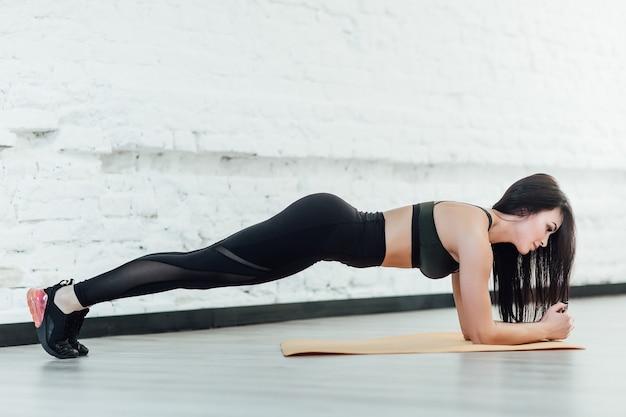 Планка упражнения на белой современной комнате. Premium Фотографии