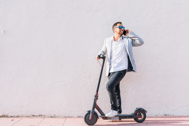 Latin adult man with sunglasses, well dressed and electric scooter talking on his mobile phone sitting on the street with a white wall background Premium Photo